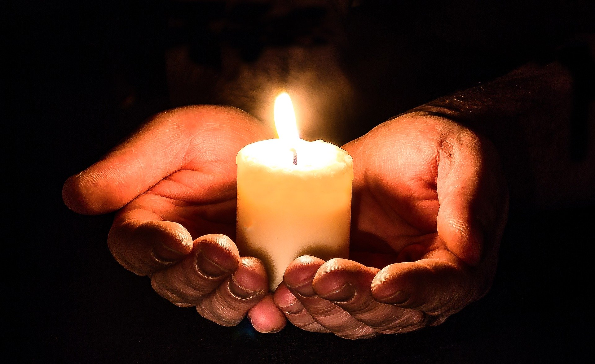 Hand and candle (Image by Myriam Zilles from Pixabay)